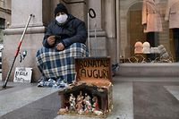 TURIN, ITALY - DECEMBER 15: A homeless person wearing a protective mask poses for a photo while wishing happy holidays on December 15, 2020 in Turin, Italy. Italy is preparing for the holiday period and while Covid-19 contagions lower, the Italian National Institute of Statistics warns of over 73,000 businesses closures, among which 13,000 are unlikely to open again due to the Covid-19 pandemic. (Photo by Stefano Guidi/Getty Images)