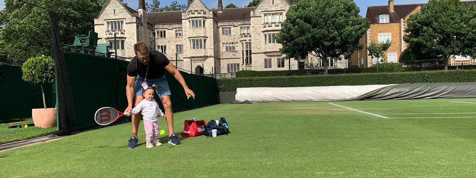 Tochter Emma darf auch schon mal probieren, wie es ist auf dem Wimbledon-Rasen zu spielen. Vater Tim zeigt, wie die Vorhand gespielt wird.