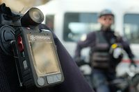 """A police officer stands guard with a body camera attached to the shoulder on February 15, 2017 in Marseille. Currently in Marseille, only the Mountain bike brigade of the city center and the Specialised field brigade (BST - Brigade specialisee de terrain) of the northern district are equipped with body cameras. Testing of the cameras began 3 years ago in France. According to th prefect of police of the Bouches-du-Rhone, Laurent Nunez, the body cameras """"reduce the tensions during interventions"""". / AFP PHOTO / BORIS HORVAT"""