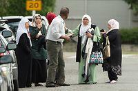 15.03.2019, Neuseeland, Christchurch: Menschen stehen nach Schüssen vor der Masjid Al Noor Moschee. Bei Angriffen auf zwei Moscheen in der neuseeländischen Stadt Christchurch sind am Freitag mehrere Menschen getötet worden. Foto: Martin Hunter/SNPA/dpa +++ dpa-Bildfunk +++