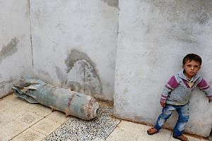 A Syrian child stands next to a deactivated bomb in his house, in the northern Syrian town of Taftana