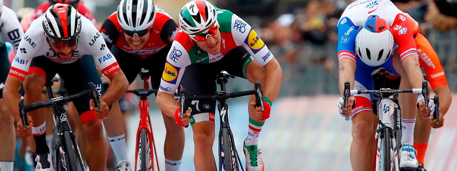 Elia Viviani (au centre, Deceuninck-Quick-Step) franchit la ligne le premier à Ortebello, mais c'est bien le Colombien Fernando Gaviria (à g., UAE) qui sera déclaré vainqueur par les commissaires