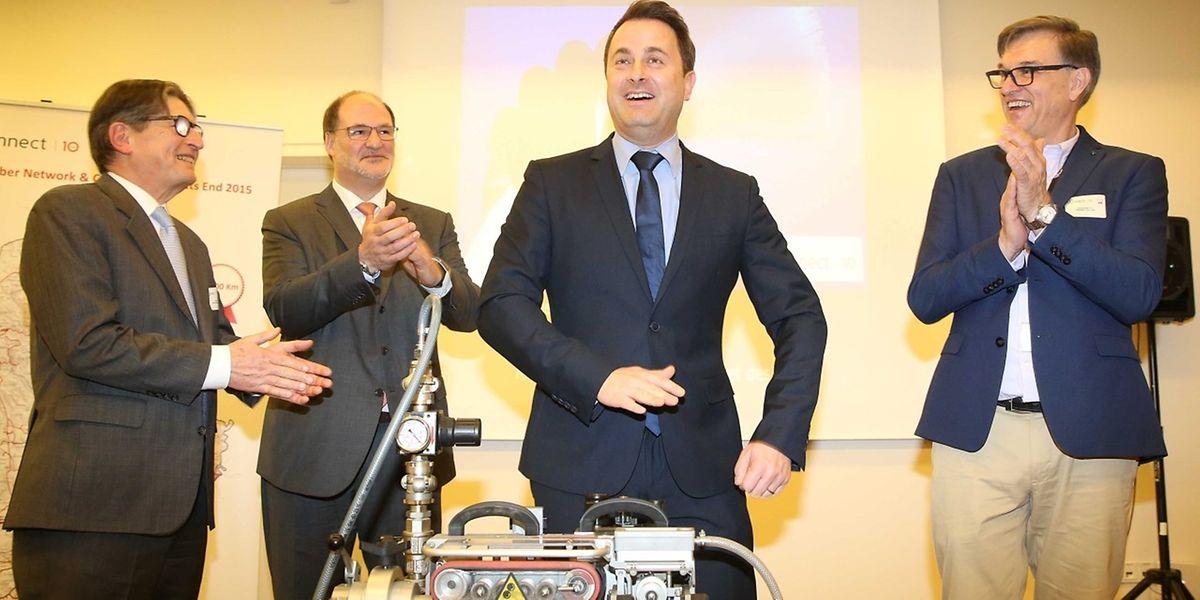 Edouard Wangen, président du conseil d'administration, Roger Lampach, p.-d.g. (à gauche) et le responsable du Fiber Network, Guy Loos, entourent le ministre des Médias et des Communications.
