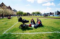 Marina and Andrea sit in the sun with their daughter Sara within a marked area at Islands Brygge in Copenhagen, on May 3, 2020 amid the novel coronavirus COVID-19 pandemic. - Marked areas are to help citizens keep distance. Each field is 40 m2 in which only 10 people can stay. (Photo by Ida Guldbaek Arentsen / Ritzau Scanpix / AFP) / Denmark OUT
