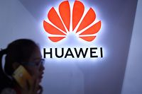 (FILES) In this file photo taken on July 8, 2018 a woman uses her mobile phone in front of a Huawei logo at Beijing International Consumer Electronics Expo in Beijing. - The chief financial officer of China's global telecommunications giant Huawei has been arrested in Canada and faces extradition to the United States, triggering a strong protest by Beijing, which called for her immediate release. (Photo by WANG ZHAO / AFP)