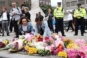 Menschen legen an der London Bridge Blumen nieder.