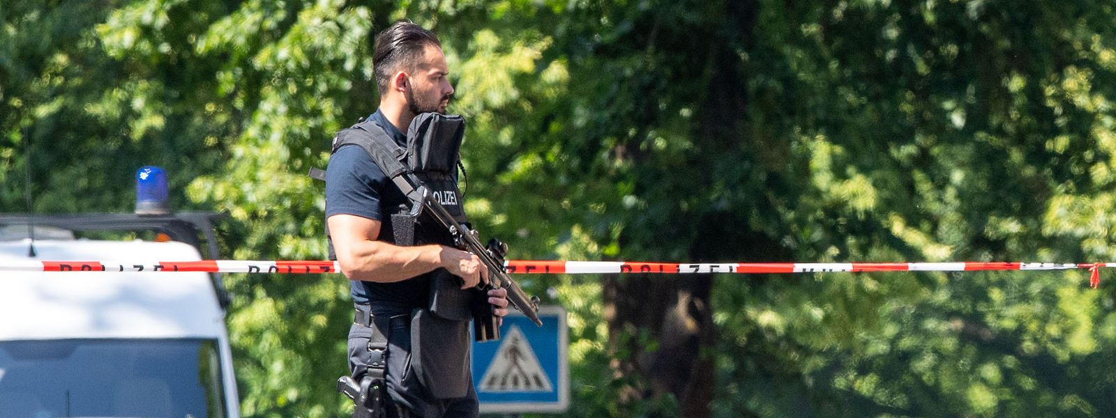 Ein Polizist mit Schutzweste und Gewehr steht an einer Absperrung in Espelkamp.