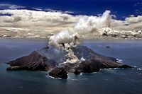 (FILES) This file photo taken on November 29, 1999 shows New Zealand's most active volcano on White Island in the Bay of Plenty giving off dense plumes of steam and gas. - New Zealand's White Island volcano erupted suddenly on December 9, 2019, prompting fears for a group of visitors seen walking on the crater floor moments before. (Photo by TORSTEN BLACKWOOD / AFP)
