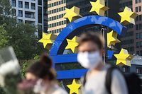 (FILES) In this file photo taken on April 24, 2020 people wearing face masks walk in front of a big Euro sign in Frankfurt am Main, western Germany, as the European Central Bank (ECB) headquarter can be seen in the background amid the coronavirus COVID-19 pandemic. - Governors of the ECB Bank are expected on September 10, 2020 to prepare the ground for new stimulus, armed with a new set of forecasts on the bloc's sluggish recovery and with the coronavirus pandemic resurging. (Photo by Yann Schreiber / AFP)