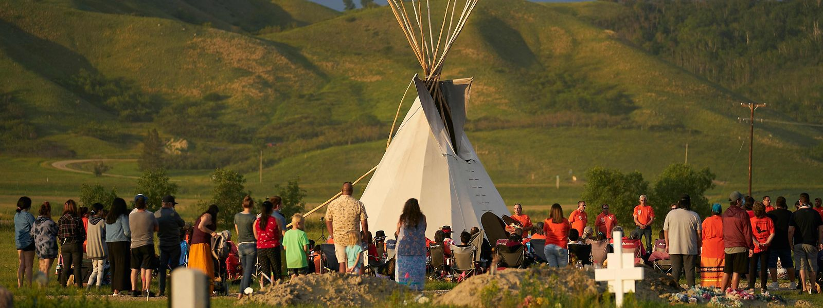 Centenas de pessoas numa vigília num campo onde foram descobertas mais de 750 sepulturas não marcadas perto de um antigo internato católico para crianças indígenas, no oeste do Canadá.