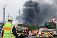 27.07.2021, Nordrhein-Westfalen, Leverkusen: Einsatzfahrzeuge der Feuerwehr stehen unweit einer Zufahrt zum Chempark über dem eine dunkle Rauchwolke aufsteigt. Nach einer Explosion seien Feuerwehr, Rettungskräfte und Polizei aktuell im Großeinsatz, erklärte die Polizei. Wegen der Schadenslage ist die viel befahrende Autobahn A1 bei Leverkusen gesperrt worden. Foto: Oliver Berg/dpa +++ dpa-Bildfunk +++