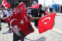 A man distributes flags with an image of the Turkish President Tayyip Erdogan to AK Party supporters during a gathering of supporters for the party's mayoral candidate Binali Yildirim in Istanbul on June 22, 2019. - Voters in Istanbul will take part in a re-run of the mayoral election on June 23, after a vote in March was annulled over alleged irregularities. Local elections around Turkey on March 31 showed the ruling party of President Recep Tayyip Erdogan remained the most popular overall, but it suffered a shock defeat in Istanbul, as well as losing the capital Ankara. (Photo by Adem ALTAN / AFP)