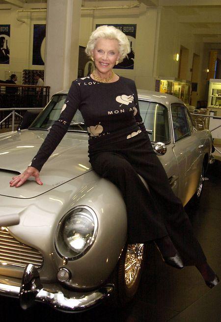 Die Schauspielerin Honor Blackman steht neben dem James Bonds Aston Martin DB5 im Wissenschaftsmuseum in London.