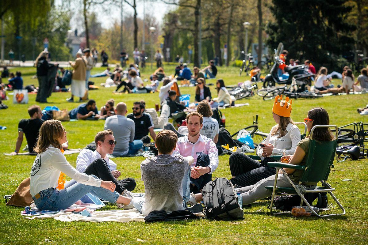 27. April: Eindhoven: Menschen sitzen am Königstag im Park Anne Frankplantsoen auf einer Wiese. Es ist der zweite «Koningsdag» im Lockdown.