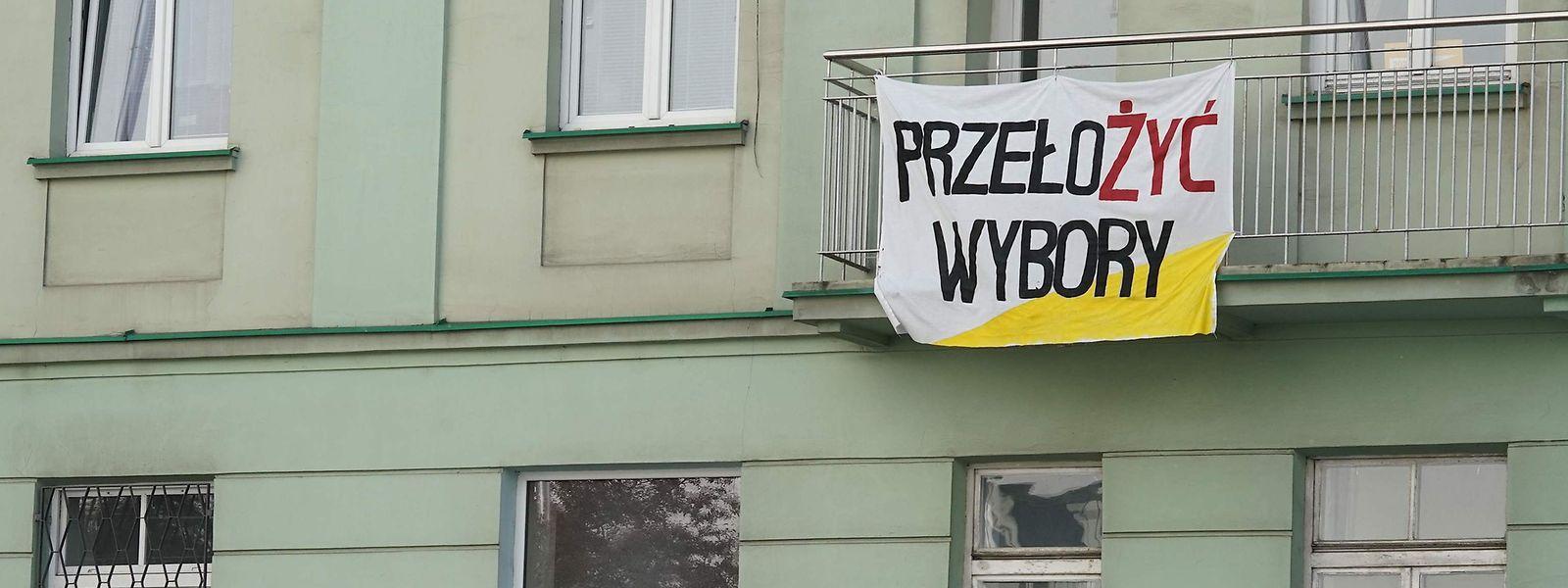 """Auf einem Banner an einer Hauswand in Warschau steht """"Wahlen verschieben!""""."""