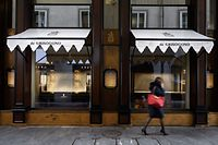 A woman walks past a store of Swiss celebrity jeweller De Grisogono with its windows empty in Geneva on January 29, 2020. - A Swiss celebrity jeweller linked to the family of Angolan ex-president Jose Eduardo dos Santos has filed for bankruptcy amid a corruption scandal involving his daughter Isabel, Bloomberg reported on Wednesday. Geneva-based De Grisogono, which has a host of international celebrity fans including Salma Hayek and Naomi Campbell, said in a statement it had not managed to secure a buyer despite months of talks, Bloomberg reported. (Photo by FABRICE COFFRINI / AFP)