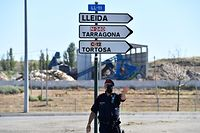 A member of the Catalan regional police force Mossos d'Esquadra controls a checkpoint on the road leading to Lleida on July 4, 2020. - Spain's northeastern Catalonia region locked down an area with around 200,000 residents around the town of Lerida following a surge in cases of the new coronavirus. (Photo by Pau BARRENA / AFP)