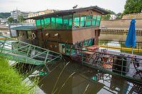 29.05.2018, Saarland, Saarbrücken: Ein früheres Restaurantschiff liegt gesunken am Saarufer nahe des Staatstheaters. Rund um das Schiff sind Ölsperren ausgelegt worden, um mögliche Umweltverschmutzungen zu vermeiden. «Bei Tageslicht muss entschieden werden, wie das Schiff geborgen wird», sagte der Sprecher. Foto: ---/BeckerBredel/dpa +++ dpa-Bildfunk +++