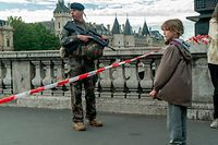 03.10.2019, Frankreich, Paris: Ein Mädchen steht vor einem bewaffneten Soldat in einer versperrten Straße nahe der Pariser Polizeipräfektur.Bei einer Messerattacke in der Präfektur wurden vier Menschen getötet. Der Angreifer war laut Medien ein langjähriger Verwaltungsmitarbeiter der Polizeipräfektur. Foto: Jair Cabrera Torres/dpa +++ dpa-Bildfunk +++