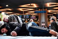 Citizens of Central Asian countries, who are stuck in Moscow after ex-Soviet states closed borders and stopped flights over the coronavirus pandemic, wait for flights to get back home at Moscow's Vnukovo airport on March 24, 2020. - With flights cancelled and borders closed, many migrant workers in Russia have found themselves trapped and unable to return to their home countries. Hundreds are stranded in airports throughout the country hoping they will be able to secure travel home. (Photo by Alexander NEMENOV / AFP)