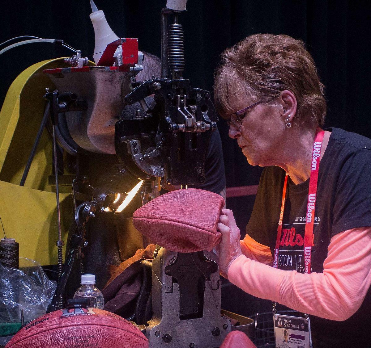 Eine Mitarbeiterin der produzierenden Firma näht die Bälle der NFL.