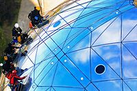 Workers scale on one of the spheres of Brussels' Atomium during a site cleaning September 28, 2012. The 102-metre (335 feet) tall structure and its nine spheres symbolise a crystal molecule of metal with its atoms being magnified about 165 billion times. The cleaning of the Atomium, which was designed for the 1958 International Exhibition of Brussels and which received a multimillion-dollar facelift in 2006, will run for a full month. A team of five specialised workers take about three days to clean a ball, each of which has a surface area of 1000 square metres (10,764 square feet). REUTERS/Yves Herman (BELGIUM - Tags: SOCIETY)