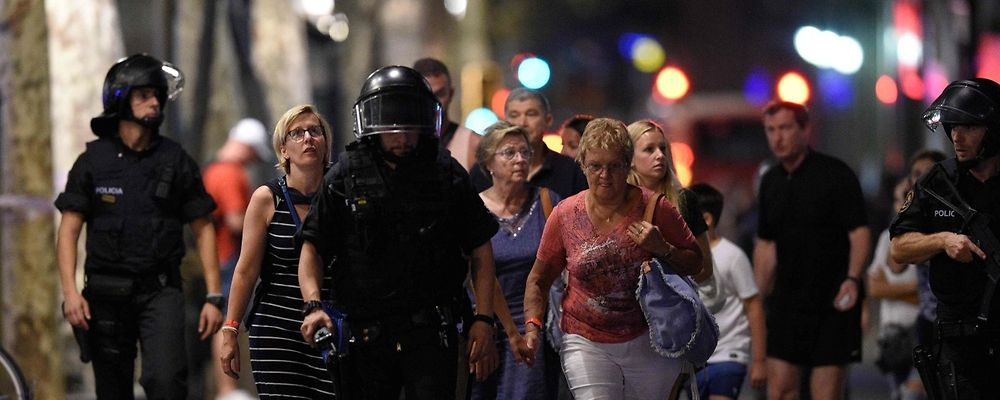 """Policemen accompany clients of a store outside a cordoned off off area after a van ploughed into the crowd, killing 13 persons and injuring over 80 on the Rambla in Barcelona on August 17, 2017. A driver deliberately rammed a van into a crowd on Barcelona's most popular street on August 17, 2017 killing at least 13 people before fleeing to a nearby bar, police said.  Officers in Spain's second-largest city said the ramming on Las Ramblas was a """"terrorist attack"""". / AFP PHOTO / LLUIS GENE"""
