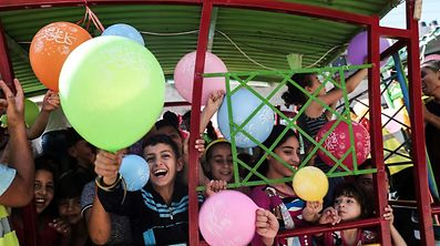 Palestinian children ride a train during an event organised by Hamas movement ahead of the Eid al-Fitr holiday marking the end of the holy Muslim fasting month of Ramadan, in Rafah, in the southern Gaza Strip, on June 24, 2017. / AFP PHOTO / SAID KHATIB