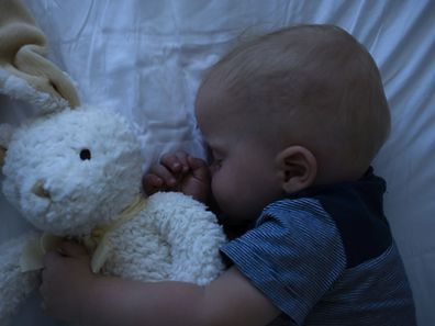 A small baby boy sleeping in his crib at night time. He is covered by a knitted blanket and is holding onto a stuffed toy. Taken at 50mp with a Canon EOS 5DSR.