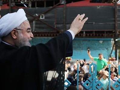"""A handout picture released by the website of the Iranian President Hassan Rouhani on May 19, 2017, shows him waving to the crowd at a polling station in Tehran during the presidential elections. / AFP PHOTO / ROUHANI.IR / HO / RESTRICTED TO EDITORIAL USE - MANDATORY CREDIT """"AFP PHOTO/HO/ROUHANI.IR"""" - NO MARKETING NO ADVERTISING CAMPAIGNS - DISTRIBUTED AS A SERVICE TO CLIENTS"""