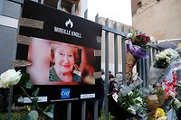 A photograph of Mireille Knoll and flowers are placed on the fence surrounding her building in Paris on March 28, 2018, in memory of the 85-year-old Jewish woman murdered in her home in what police believe was an anti-Semitic attack. The partly burned body of Mireille Knoll, who escaped the mass deportation of Jews from Paris during World War II, was found in her small apartment in the east of the city on March 23, by firefighters called to extinguish a blaze. / AFP PHOTO / FRANCOIS GUILLOT