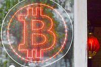 """ARCHIV - 19.06.2018, Berlin: Ein Bitcoin-Logo hängt im Schaufenster einer Kneipe in Kreuzberg. (Zu dpa """"Finanzmärkte im Bitcoin-Rausch: Digitales Gold oder Zockerwährung?"""") Foto: Jens Kalaene/ZB/dpa +++ dpa-Bildfunk +++"""