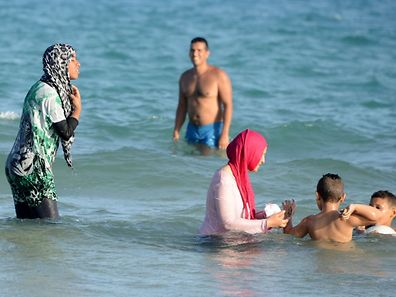 File photo shows fully covered Tunisian Muslim women swimming at Ghar El Melh beach near Bizerte, north-east of the capital Tunis
