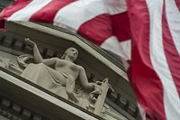 (FILES) File photo taken on July 27, 2017 shows the US national flag flying over a statue on the Department of Justice in Washington, DC. Deputy Attorney General Rod Rosenstein announced July 13, 2018 that twelve Russian intelligence officers have been indicted by a grand jury for hacking Democratic Party emails ahead of the 2016 US presidential election. The indictment was drawn up by Special Counsel Robert Mueller, the former FBI director who is looking into Russian interference in the November 2016 vote. / AFP PHOTO / ANDREW CABALLERO-REYNOLDS