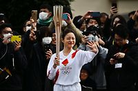 A runner waves while holding an Olympic torch during a rehearsal of the Tokyo 2020 Olympics torch relay in Tokyo on February 15, 2020. (Photo by CHARLY TRIBALLEAU / AFP)