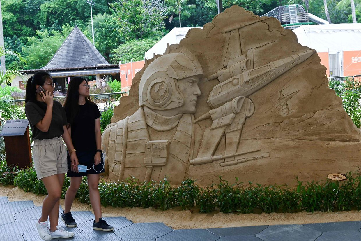 People look at sand sculptures of Star Wars characters displayed ahead of the Sentosa Sandsation Festival at Siloso beach in Sentosa Island resort in Singapore on August 30, 2019. (Photo by Roslan RAHMAN / AFP)