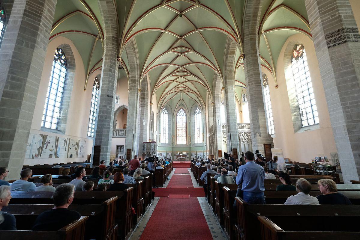Gläubige stehen während einer Andacht für einen getöteten 22-Jährigen in der St.-Jacob-Kirche. B