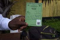 A visitor holds a Covid-19 vaccination pass at the State House in Benin City capital of Edo State, southern Nigeria on September 16, 2021. - Edo State in southern Nigeria has introduced a compulsory Covid-19 passes for access to public places and gatherings in a bid to increase vaccination rates in Africa's most populous nation. The measure which was resisted by protesters chanting anti-vaccination slogans at present is limited to workers in public service. (Photo by PIUS UTOMI EKPEI / AFP)