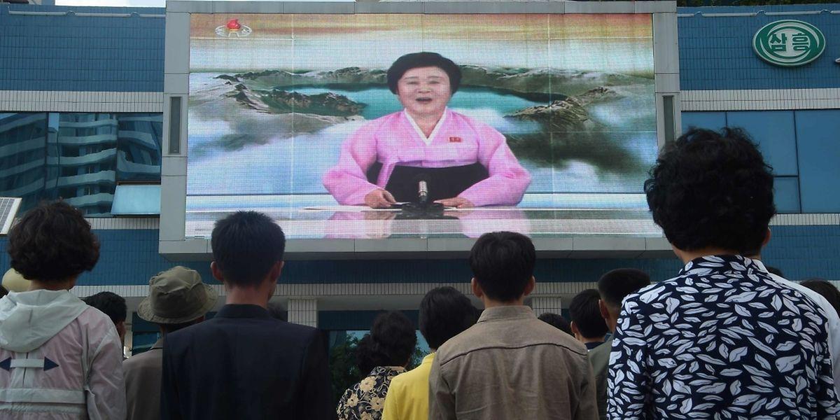 Nordkoreanische Bürger vor einem Riesenbildschirm auf dem Nachrichten ausgestrahlt werden in Pyongyang.