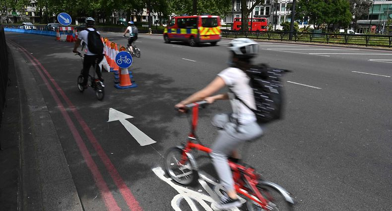 "Cyclists make use of a new expanded cycle lane on Park Lane in London on May 17, 2020, following an easing of lockdown rules in England during the novel coronavirus COVID-19 pandemic. - People are being asked to ""think carefully"" before visiting national parks and beaches on the first weekend since coronavirus lockdown measures were partially eased in England. (Photo by Glyn KIRK / AFP)"