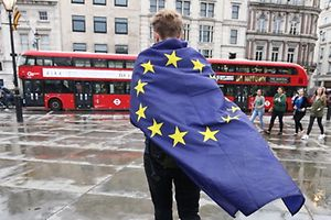 A demonstrator wrapped in a European flag leaves an anti-Brexit protest in Trafalgar Square in central London on June 28, 2016. EU leaders attempted to rescue the European project and Prime Minister David Cameron sought to calm fears over Britain's vote to leave the bloc as ratings agencies downgraded the country. Britain has been pitched into uncertainty by the June 23 referendum result, with Cameron announcing his resignation, the economy facing a string of shocks and Scotland making a fresh threat to break away. / AFP PHOTO / JUSTIN TALLIS