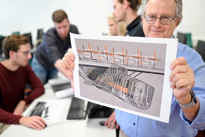 Ingenieur und Informatiker Peter Kielhorn (r) hält eine Seitenansicht des Flugbootes DO X.