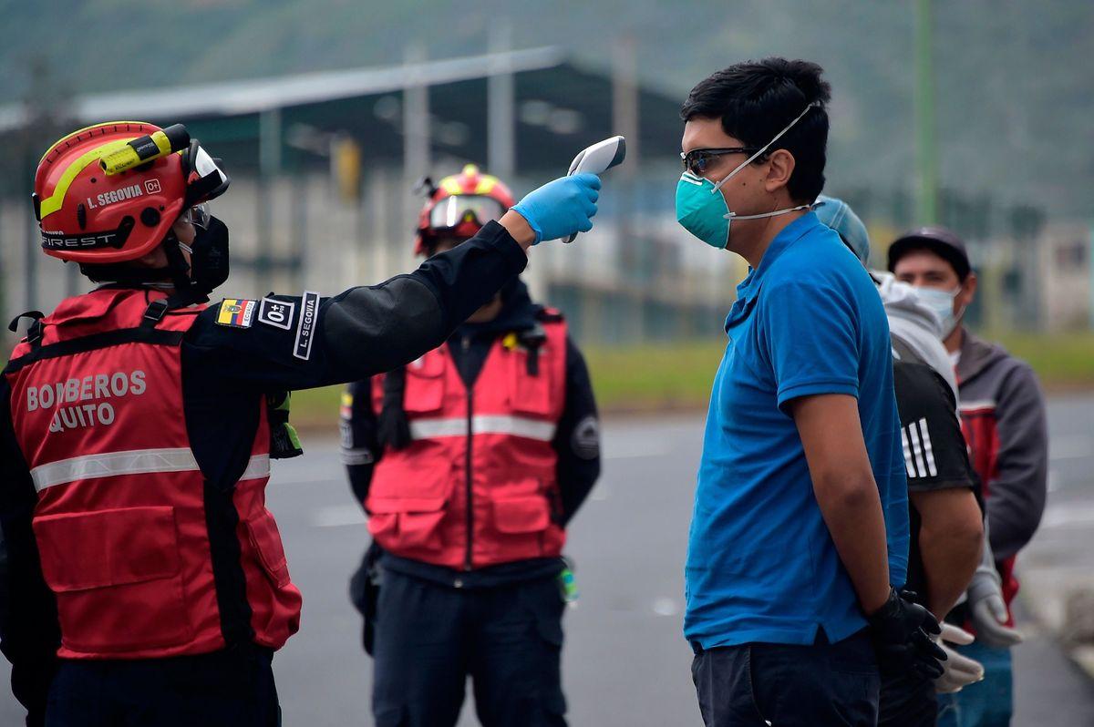 Ein Feuerwehrmann misst die Körpertemperatur eines Passanten in Guayaquil.