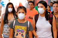 Passengers wear protective face masks as a precaution against the spread of the new Coronavirus, COVID-19, at Jorge Chavez International Airport, in Lima, on March 6, 2020. - Peruvian Government confirmed its first case of Coronavirus. President Martin Vizcarra reported that it is a 25-year-old male patient, who arrived from a trip to Spain, France and the Czech Republic. (Photo by Luka GONZALES / AFP)