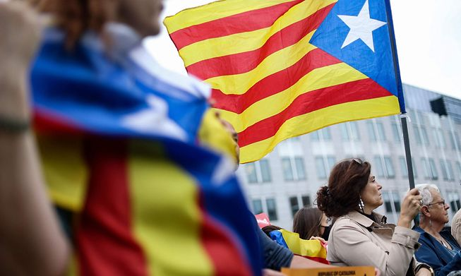 A woman holds a flag of Catalonia during a demonstration near the European Parliament in Brussels on Friday after the exiled former Catalan president Carles Puigdemont was arrested in Italy