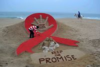 (FILES) In this file photograph taken on November 29, 2013, Indian sand artist Sudersan Pattnaik gives the final touches to a sand sculpture on the eve of World AIDS Day, as a horseman rides by on Golden Sea Beach in Puri, some 65 kms east of Bhubaneswar. - HIV-related deaths last year fell to around 770,000 -- some 33 percent lower than in 2010 -- the United Nations said July 15, 2019, but warned that global efforts to eradicate the disease were stalling as funding dries up. An estimated 37.9 million people now live with HIV -- a record 23.3 million of those have access to some antiretroviral therapy (ART), UNAIDS said in its annual report. (Photo by ASIT KUMAR / AFP)
