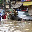 Pakistan, Lahore:Männer und Kinder schieben ein Auto über eine überflutete Straße.