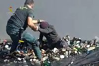 """An handout image released by the Spanish Guardia Civil on February 22, 2021 shows a member of the Spanish Guardia Civil discovering an aspiring migrant hidden in a container full of broken glass for recycling  at the port in Spain's Melilla enclave on Morocco's northern coast, on February 19, 2021. - Police discovered a total of 41 migrants at the port trying to illegally board boats to the Spanish mainland on February 19, 2021, hidden in lorries and other vehicles. (Photo by Handout / Spanish Guardia Civil / AFP) / RESTRICTED TO EDITORIAL USE - MANDATORY CREDIT """"AFP PHOTO /HANDOUT/SPANISH GUARDIA CIVIL """" - NO MARKETING - NO ADVERTISING CAMPAIGNS - DISTRIBUTED AS A SERVICE TO CLIENTS"""