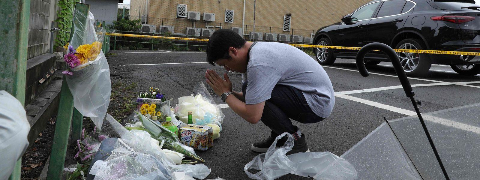Ein Mann legt Blumen neben dem ausgebrannten Gebäude nieder und betet.