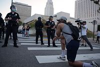 TOPSHOT - A demonstrator kneels in front of a row of police officers as protesters gather in downtown Los Angeles on May 27, 2020 to demonstrate after George Floyd, an unarmed black man, died while being arrested by a police officer in Minneapolis who pinned him to the ground with his knee. - Outrage has grown across the country at Floyd's death on May 25, fuelled in part by bystander cellphone video which shows him, handcuffed and in the custody of four white police officers, on the ground while one presses his knee into the victim's neck. (Photo by Agustin PAULLIER / AFP)